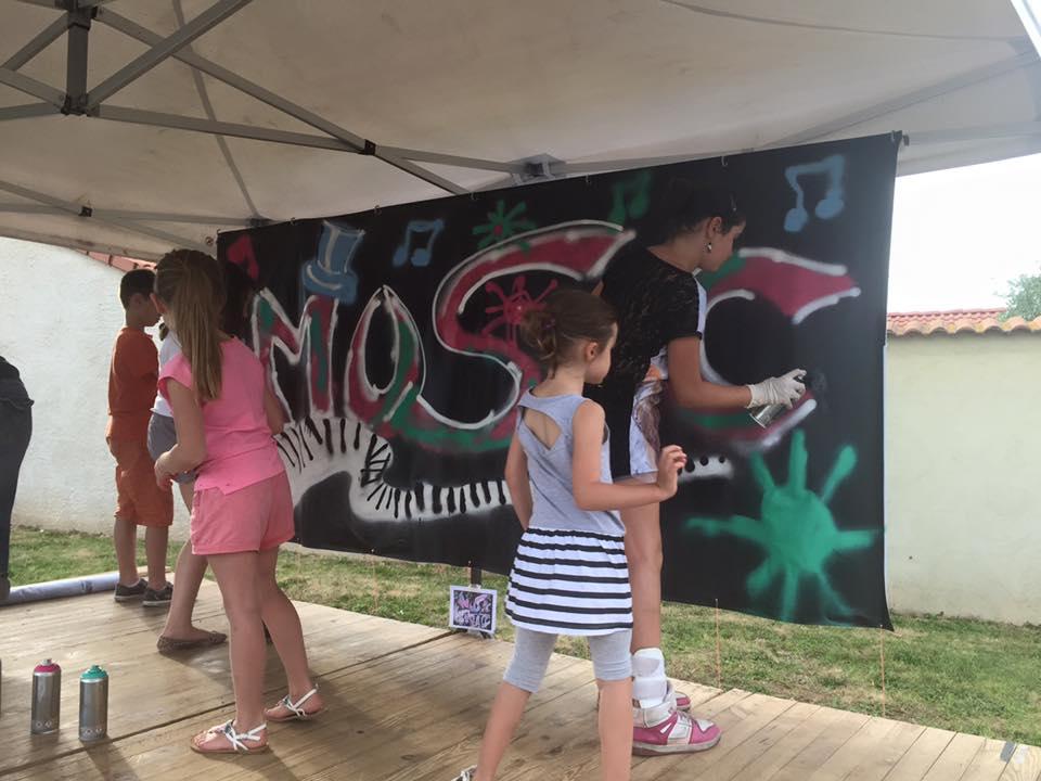 Groupe d'enfants réalisant une fresque avec des bombes de peinture