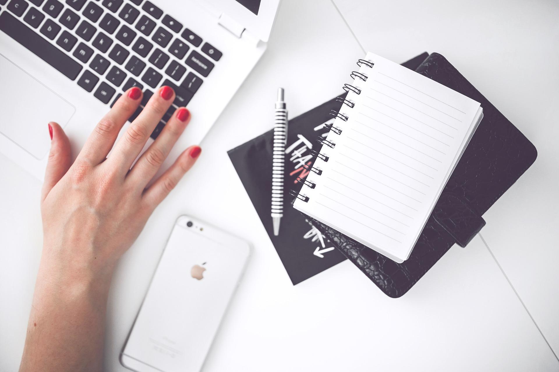 Calepin, téléphone et ordinateurs disposés sur un bureau